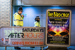 """© Licensed to London News Pictures . 19/12/2014 . Manchester , UK . Police attend at the Bird Cage on Withy Grove . """" Mad Friday """" revellers out in the rain and cold in Manchester . Mad Friday is typically the busiest day of the year for emergency services , taking place on the last Friday before Christmas when office Christmas parties and Christmas revellers enjoy a night out .  Photo credit : Joel Goodman/LNP"""