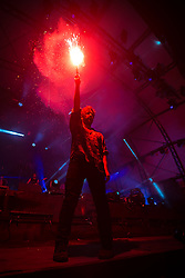© Licensed to London News Pictures . 21/07/2013 . Suffolk , UK . Yannis Philippakis with a red flare . Foals play at the Obelisk Arena as the closing act on the festival's main stage . The Latitude music and culture festival in Henham Park , Southwold . Photo credit : Joel Goodman/LNP