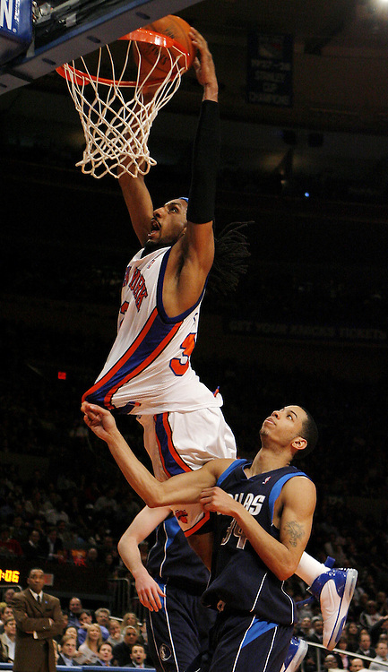 The Knicks' Renaldo Balkman (L) dunks over the Mavericks' Devin Harris (R)  during the first half of the game between the Dallas Mavericks and the New York Knicks at Madison Square Garden in New York, New York on Tuesday 20 March 2007.