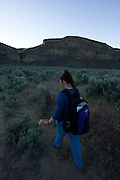 Forest Service wildlife technician Aimee Hart walks a path that leads to Dutch Henry Falls in the desert of Central Washington. Aimee will assist in the capture of bats during a bat survey that will take place at the falls. The Nature Conservancy's Dutch Henry Falls, Washington.