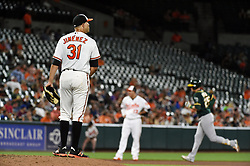 August 22, 2017 - Baltimore, MD, USA - Baltimore Orioles pitcher Ubaldo Jimenez, left, watches as the Oakland Athletics' Ryon Healy, right, rounds the bases after a two-run home run in the fifth inning at Oriole Park at Camden Yards in Baltimore on Tuesday, Aug. 22, 2017. The A's won, 6-4. (Credit Image: © Kenneth K. Lam/TNS via ZUMA Wire)