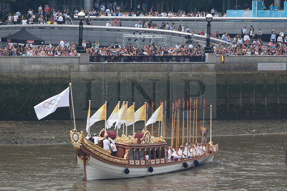 © licensed to London News Pictures. London, UK 27/07/2012. The Olympic Torch on Gloriana approach to the Olympic Rings outside the City Hall as its being carried along River Thames to make the final leg of its epic 8,000 mile journey. Photo credit: Tolga Akmen/LNP