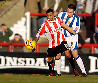 Photo: Leigh Quinnell.<br /> Brentford v Huddersfield Town. Coca Cola League 1. 21/01/2006. Huddersfields David Mirfin keeps hold of Brentfords Dudley Campbell.