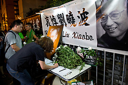 July 13, 2017 - Hong Kong, Hong Kong SAR, China - People gather to sign the condolence book. Following the death in China of Liu Xiaobo, the Nobel peace laureate, people protest outside the Liaison Office of the Central People's Government in the Hong Kong Special Administrative Region. (Credit Image: © Jayne Russell via ZUMA Wire)