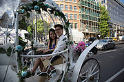 Chinese wedding couple in a horse drawn Cinderella carriage on Lower Thames Street in London, UK. It is a common site now to see extravagant and visual elements to Asian weddings in the UK.