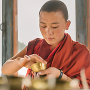 A nun lighting candles.<br /> The Sangchhen Dorji Lhuendrup Nunnery is perched on a hilltop overlooking the Punakha valley and Wangduephodrang valley. The nunnery has several hundred women staying and studying the principles of buddhism.