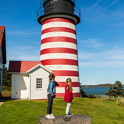Two sisters play outside the West Quoddy Head Lighthouse in Lubec, Maine. Easternmost point in the United States.