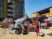 "15 FEBRUARY 2019 - SIHANOUKVILLE, CAMBODIA: A Cambodian construction laborer walks through worker housing next to the site of the Chinese casino construction site she works at. There are about 80 Chinese casinos and resort hotels open in Sihanoukville and dozens more under construction. The casinos are changing the city, once a sleepy port on Southeast Asia's ""backpacker trail"" into a booming city. The change is coming with a cost though. Many Cambodian residents of Sihanoukville  have lost their homes to make way for the casinos and the jobs are going to Chinese workers, brought in to build casinos and work in the casinos.    PHOTO BY JACK KURTZ"