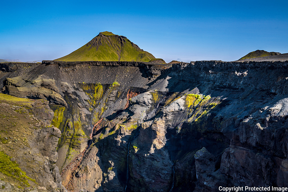 Streaks of colour brighten the gully of the river Markarfljót in south <br /> Iceland, with the mountain Hattfell in the background.