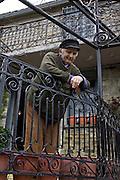 Greece, Epirus, Zagoria Man looking out of his balcony