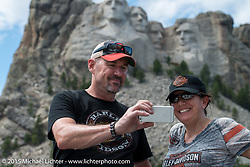 Marilyn and Chris Monnette of Lafayette, CO take a selfie with the faces at Mt Rushmore National Monument during the 75th Annual Sturgis Black Hills Motorcycle Rally.  SD, USA.  August 8, 2015.  Photography ©2015 Michael Lichter.