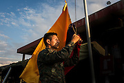 2016/07/27 – Portoviejo, Ecuador: A corporal from the Ecuadorian army takes down the country flag at sunset on the shelter located at the old airport of Portoviejo, Ecuador, 27th July 2016. (Eduardo Leal)