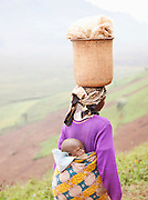 A woman of the Batwa tribe carrying her child and food. The Batwa are a pygmy people who were the oldest recorded inhabitants of the Great Lakes region of central Africa. South West Uganda