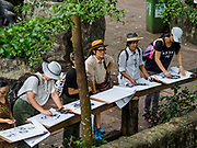 17 AUGUST 2018 - BANGKOK, THAILAND:   A group of artists draw Malayan sun bears on display in Dusit Zoo in Bangkok. The zoo opened in 1938. The zoo grounds were originally the Dusit Royal Garden. The zoo is scheduled to close by the end of August 2018 because it is being relocated to Nakhon Pathom province, south of Bangkok.     PHOTO BY JACK KURTZ