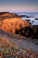 Sunset light and path on top of rocky coastal bluffs over the Pacific Ocean, Piedras Blancas, near San Simeon, California