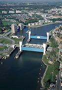 Nederland, Zuid-Holland, Capelle aan den IJssel, 08-03-2002; stormvloedkering in de Hollandsche IJssel. Bij storm en dreigend hoog water wordt een van de twee schuiven naar beneden gelaten, de tweede schuif dient al reserve. De scheepvaart kan de gesloten kering paseren via de naastgelegen schutsluis. De stormvloedkering maakt deel uit van de Deltawerken en is als eerste voltooid in 1958. Ten tijde van De Ramp - watersnood 1953 - werd het zeewater door de storm opgestuwd en dreigde de verzwakte rivierdijken in het achterland het te begeven waardoor grote van het laag gelegen westen van Nederland ondergelopen zouden zijn. De flats staan links staan in Capelle a/d IJssel, rechts Krimpen aan den IJssel..Netherlands, Capelle at the river IJssel, near Rotterdam: storm surge barrier, protects the highly populated western part of Holland, which lies below sea level. In case of storm and threat of high water, one of the two doors is lowered into the river (the second door is a spare one). The lock next to the barrier allows shipping when the barrier is closed...luchtfoto (25 procent toeslag); aerial photo (additional fee required)..foto Siebe Swart / photo Siebe Swart
