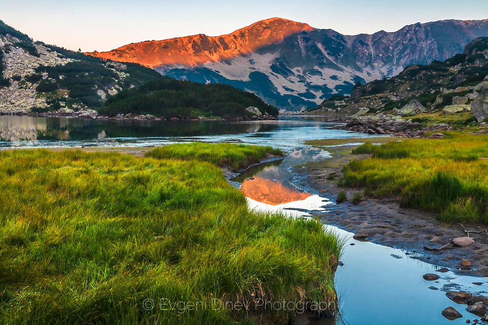 Summer sunrise by a lake in the mountain