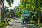 A motorised rickshaw travels down a rural road fully loaded with a delivery on the 2nd of October 2018 in Satkhira District, Bangladesh. Satkhira is a district in southwestern Bangladesh and is part of Khulna Division. It lies along the border with West Bengal, India. It is on the bank of the Arpangachhia River. The largest city and headquarter of this district is Satkhira.