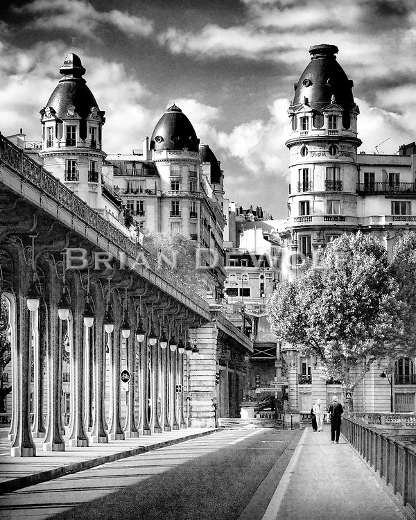 Looking North from the Bir Hakeim bridge in Paris, France.  The Eiffel Tower is over the behind and to the right of the photographer's shoulder. The sunlight plays among the  buildings and columns.  Aspect Ratio 1w x 1.25h.