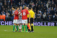 Swansea city capt Garry Monk (16) and Angel Rangel have words with referee Lee Mason and his assistants at the end of the match after the officials had disallowed a 'goal' scored by Swansea player Roland Lamah. Barclays Premier league, West Bromwich Albion v Swansea city at the Hawthorns stadium in West Bromwich, England on Saturday 9th March 2013.  pic by  Andrew Orchard, Andrew Orchard sports photography,
