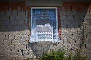 A new window with a curtain and an undone facade at the village of Rankovce, close to Kosice in eastern Slovakia. The foundation ETP Slovakia has a project in Rankovce setting up micro-loan funds for the local Roma community. Loans from this fund enable families to build their own low-cost brick homes, on land they own. The families are committed to radically improve their living conditions.