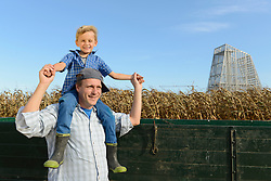 Father carrying his son on shoulders in cornfield, geothermal power station in background, Bavaria, Germany