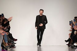 Designer David Koma greets the audience after presenting his Autumn/Winter 2017 London Fashion Week show at the BFC Space Show, London.