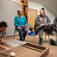 Diné weaver Lois A. Becenti, seated left, with Diné Be´ iinà – The Navajo Lifeway sits with Kobe Sam, seated center, and her aunt Brooke Smith while John Lateyice of Zuni prepares his warp Friday, Jan. 17 at a free Navajo rug weaving class led by Becenti at the Octavia Fellin Public Library in Gallup. Becenti will host free rug weaving classes Friday Feb. 21 and Friday March 20 from 10 am to 3 pm at the Octavia Fellin Public Library in Gallup.