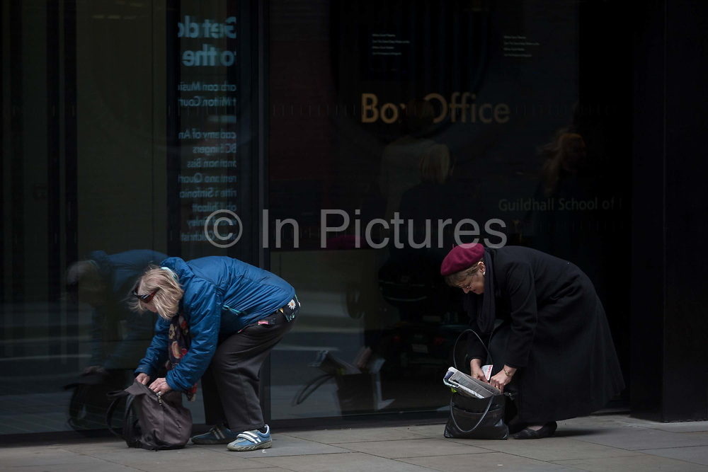 Two women both bend to search for items in their bags, outside a box office entrance, on 16th February 2017, in the City of London, England.