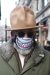© Licensed to London News Pictures. 15/12/2020. London, UK. A Christmas shopper wears a cowboy hat and a shark themed face mask as he walks along Regent Street in London's West End. London and other areas of the south east are to enter tier three restrictions at midnight tonight as Covid-19 infection rates rise. Photo credit: Peter Macdiarmid/LNP