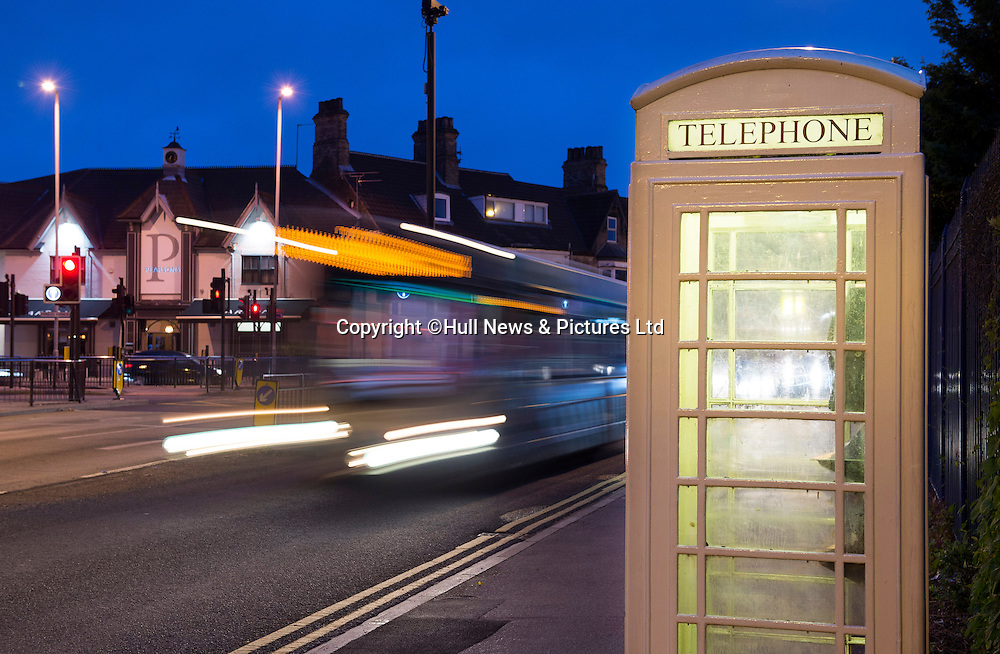 22 June 2015: A cream KC phone box lit up at night on Spring Bank, Hull,  with cars and buses streaming past.<br /> Picture: Sean Spencer/Hull News & Pictures Ltd<br /> 01482 772651/07976 433960<br /> www.hullnews.co.uk   sean@hullnews.co.uk