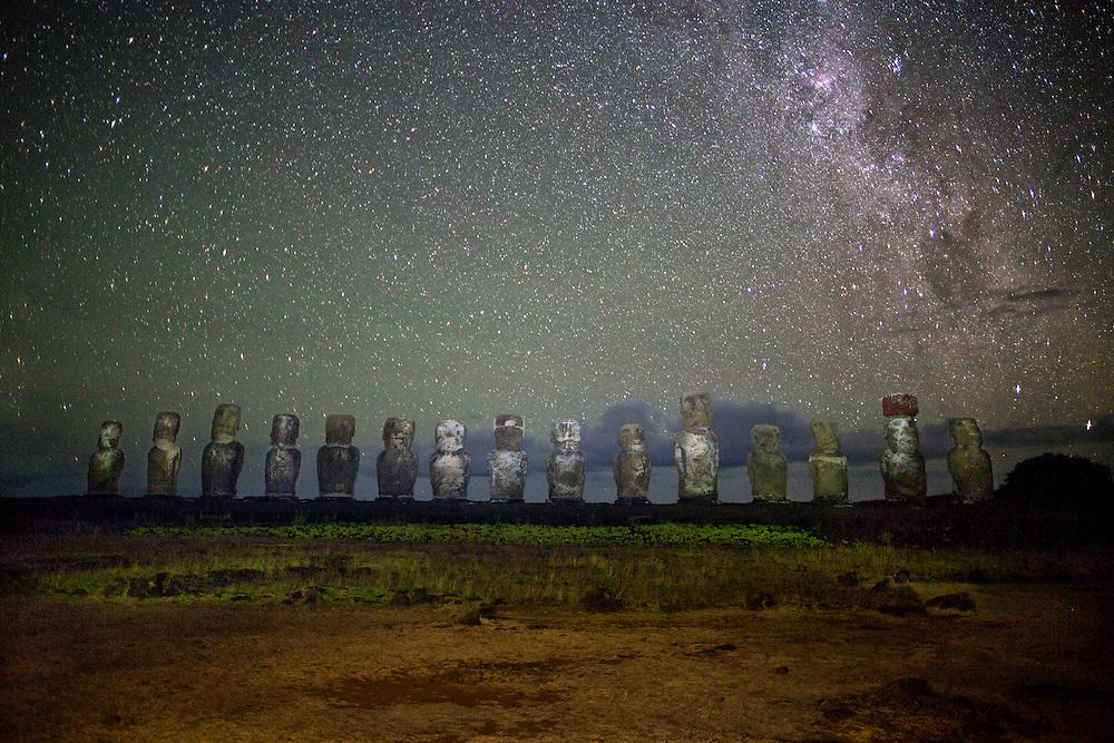 Moai statues stand tall at Tongariki at night under the Milky Way Galaxy.