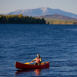 A man paddles his canoe on Seboeis Lake near Millinocket, Maine.  Mount Katahdin is in the distance.
