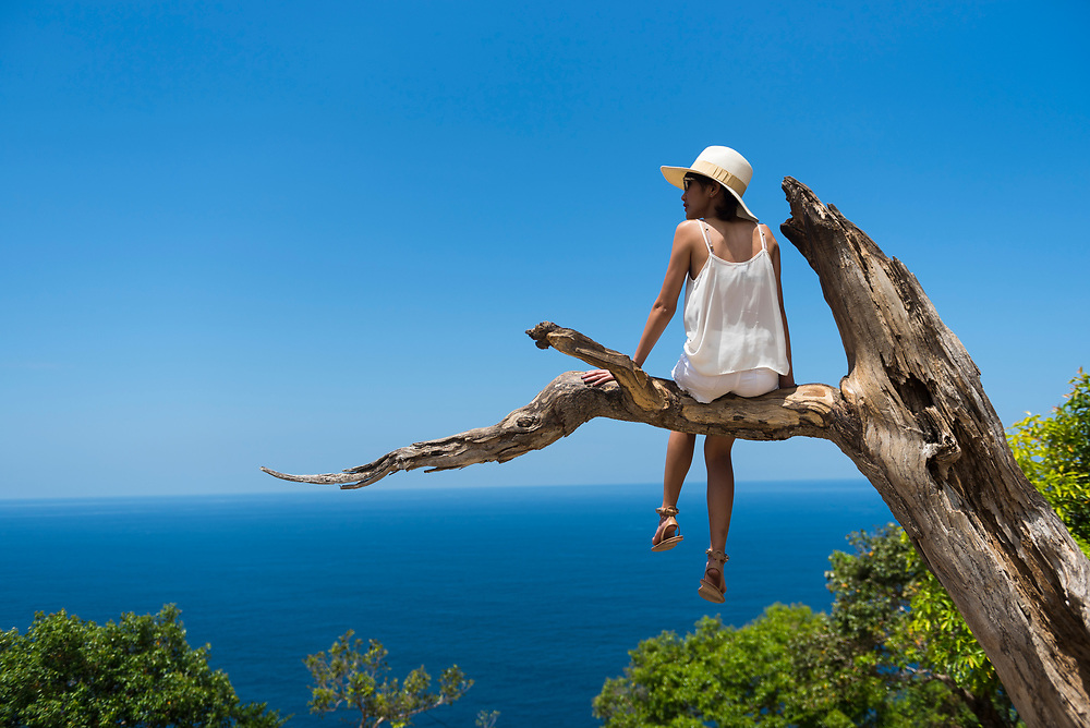 Nusa Penida, Indonesia - October 3, 2017: A young Thai woman visiting Indonesia enjoys the dramatic view from atop a tree limb at Kelingking Beach, located on the island of Nusa Penida near Bali.