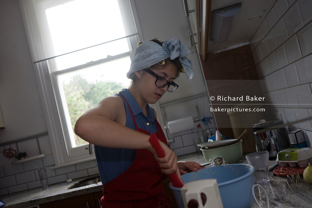 A 15 year-old teenager bakes party cakes in a domestic kitechen.