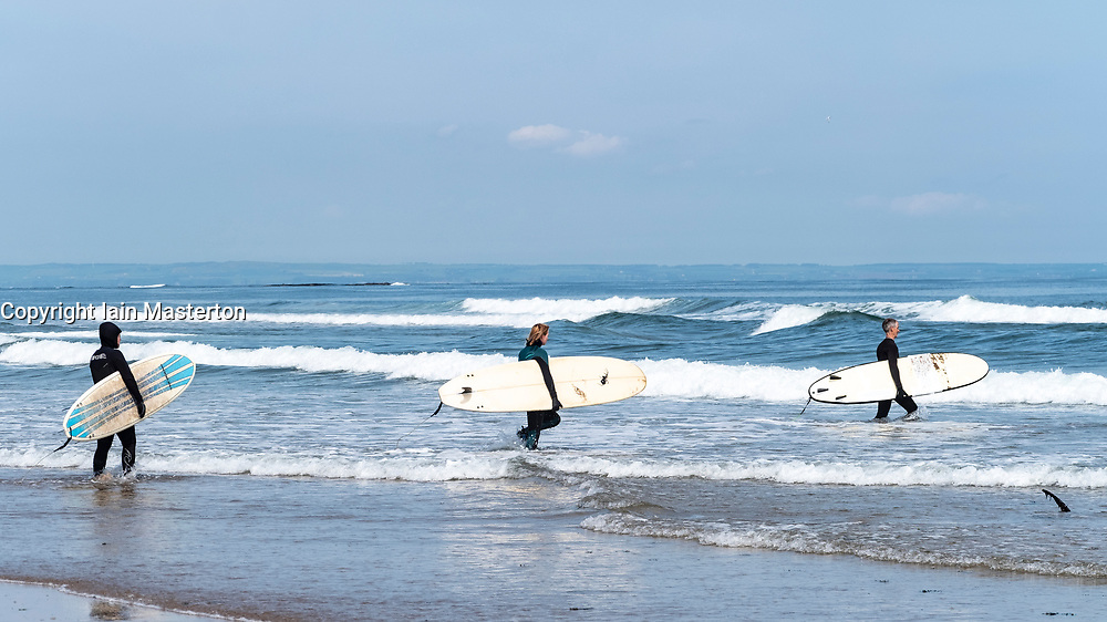 Surfers carry surfboards to sea at Belhaven Beach, Bass Rock in distance, East Lothian, Scotland, United Kingdom