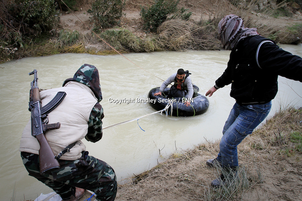Members of the Free Syrian Army move weapons, medicine and personnel across a river near Al Janoudiyah, Idlib province, Syria.
