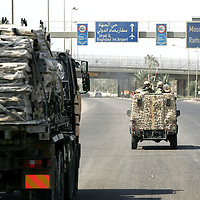 Baghdad, Iraq, 2 Oct 2005. Running 'Route Irish'...An armoured Land Rovers escorts a supply truck.....B Company, 1st Battalion, The Royal Irish Regiment, a tight-knit multi national fighting force make daily escorting runs along ?Route Irish?, the infamous Baghdad Airport road. The 46 man team are all British Army regulars but come from as far afield as Fiji, South Africa and Northern and Southern Ireland. Previous deployments in Kosovo, Sierra Leone and Northern Ireland have equipped them with the valuable skills needed to provide protection for British Forces and materials transiting the world?s most dangerous highway. Due to an increased presence of US forces along the route both in dug in positions and mobile patrols, attacks along the road have slackened, despite this a day rarely passed without an IED (improvised explosive device) being detonated or a small arms attack against coalition forces. ..The convoy attempts to maintain a seclusion ?bubble? around its vehicles for the duration of the journey. Any civilian vehicle that either strays into the bubble or refuses to keep their distance represents a threat and should they ignore the warning blasts on air horns carried in each vehicle the rules of engagement progress from warning shots to use of lethal force. The relative safety of the International Zone offers them an opportunity to decompress between missions. A duty driver ferries soldiers to the ?Liberty Pool?. Once only frequented by Iraq?s Ba?athist elite the luxury swimming pool and gym now fills with troops. Their body armour, helmets and weapons all within easy reach they either soak up the sun or compete with each other in diving competitions. After a daily briefing the troops have access to the ?Mosquito and Camel? bar where they watch TV or play pool and in accordance with the ?2 can rule? are allowed to drink 2 beers per night.