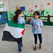 Girls draped in the Palestinian flag in El-Buss refugee camp. Developmental Action Without Borders(Naba'a) work in Palestinian refugee camps across Lebanon to help children in the camps.  The camps are densely over-crowded and many of the children are 4th generation refugees living in Lebanon with no citizenship or rights and under immense pressure. Naba'a is a mix of Palestinians and Lebanese and aim to give children a sense of security and freedom to express their needs and rights.Naba'a operates in communities governed by a multitude of political parties and religious groups and Naba'a keeps a strict independed line from any affiliation with any groups.