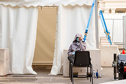 © Licensed to London News Pictures; 15/09/2020; Bristol, UK. A member of staff sitting on two chairs covers his face at a Covid-19 Walk-through Testing Site in the Bristol Victoria Rooms Car Park. Amid reports of a national shortage in the covid-19 coronavirus pandemic testing system Bristol City Council has said that ongoing problems with a shortage of available coronavirus tests in the Bristol area will take weeks to resolve. There are unconfirmed reports that last week there were no tests happening at the Victoria Rooms site. NHS Providers have said that hospitals in Bristol raised concerns over staff absences because of the lack of testing. In some parts of the UK people are being asked to drive hundreds of miles for a test despite sites being available closer to them. Bristol recently recorded the biggest daily increase in 10 weeks of new cases of coronavirus, and nationally there was the highest rise for four months. Photo credit: Simon Chapman/LNP.