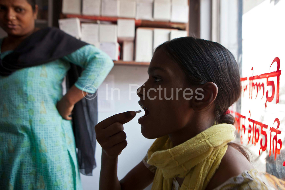 A patient swallows Tuberculosis (TB) medication in Delhi, India. The treatment for TB is a minimum 6 month course of combination antibiotics that must been taken everyday, otherwise fatal drug resistance can develop.  The medication is free and provided by the government. TB is an infectious disease and a huge public health issue often associated with poverty.  TB is completely curable, however TB rates are increasing and India suffers from the highest burden of TB in the world.