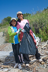 United States, Washington, Seattle, Discovery Park, mother and daughter (age 8) with garbage from beach clean-up community service project with Social Venture Partners.   MR