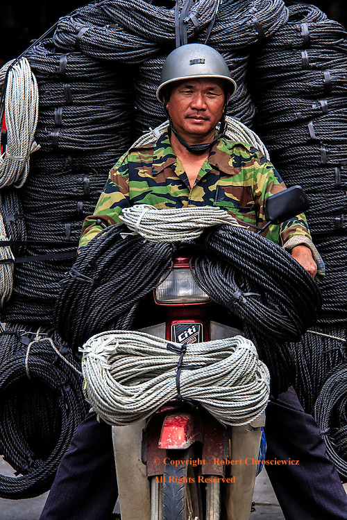 Roped In:  A man is dwarfed by his product as he is about to transport a seemingly impossible amount of coiled rope on his small motorbike, in the central market of Hoi An Vietnam.
