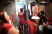 In this photo taken May 25, 2011, Dara, second right, drinks with a customer as other sex workers get ready at the Vila Mimosa prostitution zone in Rio de Janeiro, Brazil. <br /> <br /> Spelling the possible end of Vila Mimosa is a high-speed train the government wants to build to link Rio to Sao Paulo, as part of Brazil's Olympic proposal. The government is expected to open bidding to prospective builders July 29.