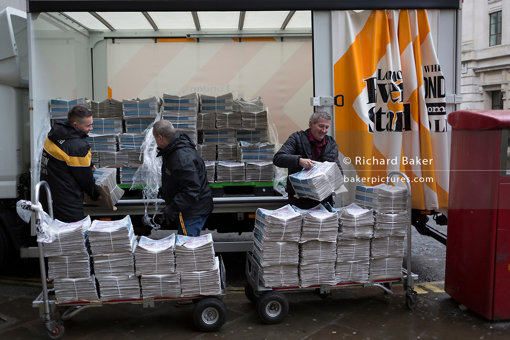 Newspaper delivery men unload a van of Evening Standard first editions onto trolleys for distribution in the Bank area in the City of London, the capital's financial district, 7th March 2018, in London England.