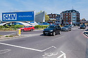 A simple billboard advert  says SHN (NHS in reverse) #StayHomeNow and yet Vauxhall cross is failry busy with a steady stream of vehicles - The 'lockdown' continues in London because of the Coronavirus (Covid 19) outbreak.
