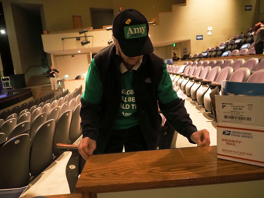 An Amy Klobuchar supporter prepares a sign for hanging to let caucus goers where to sit.