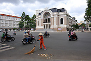 A street cleaner goes about her work oblivious to the traffic moving around her. In the background is the Saigon Opera House (Nha hat lon Thanh pho Ho Chi Minh). Built in 1897 by French architect Ferret Eugene, this 800 seat building was used as the home of the Lower House assembly of South Vietnam after 1956. It was not until 1975 that it was again used as a theatre, and it was fully restored in 1998. Ho Chi Minh City (Saigon), Vietnam