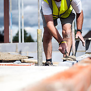 Building Site location Photography focusing on a close up shot of a bricklayers hands