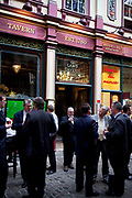 City workers having a drink outside The Lamb Tavern pub in Leadenhall Market in the City of London. Located in Gracechurch Street, the market dates back to the fourteenth century. There are cheesemongers, butchers and florists. Originally a meat, game and poultry market, it stands on what was the centre of Roman London. Designed in 1881 by Sir Horace Jones.